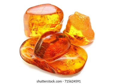 Few pieces of amber with different inclusions,  beetle,  fly,  mosquito,  ant,  larva. Several pieces of amber on a white background. Sunstone with insects . Ancient insects inside fossil pitch.