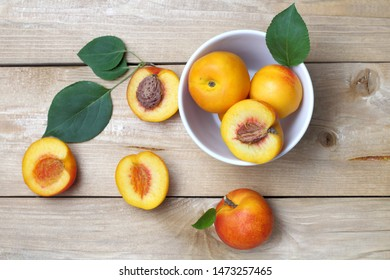 A few pieces of nectarines or apricots top  view close-ups on a table made of wood, a slightly dark background, a cut with a stone. Rustic lifestyle. Bright natural colors, high contrast.
