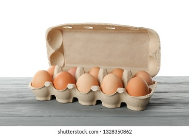 Few raw chicken eggs in carton box on wooden table against white background