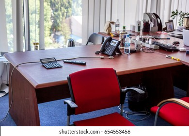 Few red leather armchairs with wooden handle near brown wooden table with many black open laptops and work desk with shits of paper in a meeting room against window, office landscape in meeting room