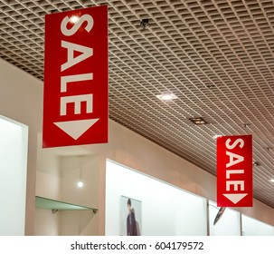 few red vertical sale posters with white letters hang from grid ceiling in big shop in sale season. sale poster board at fashion clothes shopfront