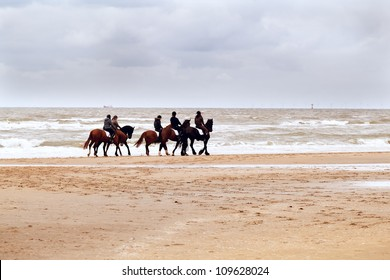 few riders on horses on the beach close to North sea