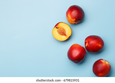 A few ripe red nectarines on a blue background