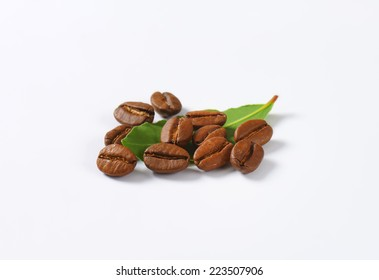 few roasted coffee beans with green leaves