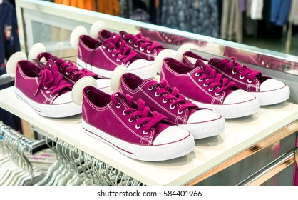 few rows of colorful burgundy violet sneakers with such color shoe lines with round security magnet tag wait for its buyers on white market shelf against another clothes. lots of sneaker shoes on sale