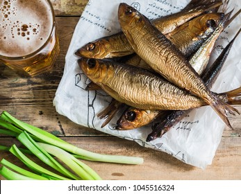 A few smoked Baltic herring on white paper and beer in glass on an old wood  background. Top view