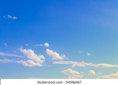 Few soft clouds in bright blue sky