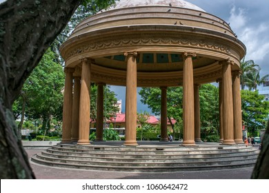 "A few steps lead up to a circular pavilion in the Morazán Park, Costa Rica. It is called ""Temple of Music"", a replica of the ""Temple of Love and Music"" located in the Palace of Versailles, France."