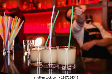A few sweet cocktails on the bar, against the cheerful bartender pointing to the person.