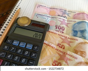 a few turkish lira banknotes on the table, minimum wage on the calculator screen
