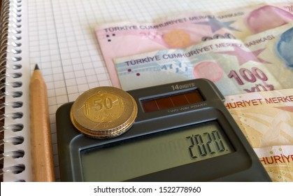 a few turkish lira banknotes on the table, minimum wage on the calculator screen, coins on the calculator