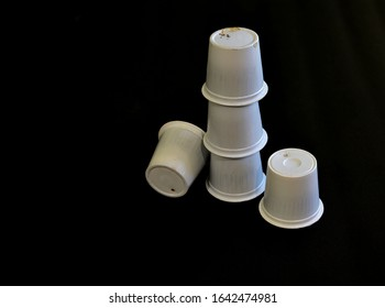A few used white coffee pods ready for recycling.