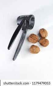 a few walnuts and a nutcracker isolated on white