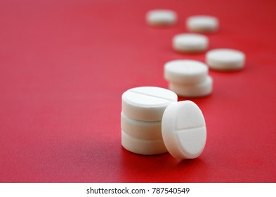 A few white tablets lie on a bright red background surface. Background image on medical and pharmaceutical topics