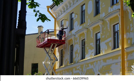 A few workers are restoring a yellow facade of a building from crane lifter.