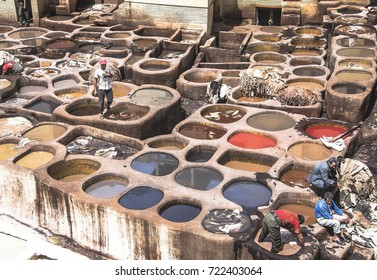 Fez, Morocco. 25 June 2015 -  Man working as a tanner in the dye pots at leather tanneries viewed from from the Terrace de Tanneurs in the ancient medina, Fes el Bali, in Fez, Morocco.