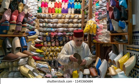 Fez, Morocco - April 2018: Unkown man selling slippers and shoes in traditional store in Fes, Morocco