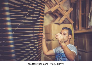 FEZ, MOROCCO - AUGUST 25, 2018 : Moroccan weaver works on textiles in a store of scarfs in the Fez medina