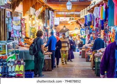 FEZ, MOROCCO - DECEMBER 10: Bazaar with clothes and food for sale in Fez medina aka. old town. December 2016