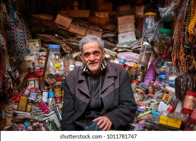 Fez / Morocco - December 19th 2016: Deep inside the old medina of Fez, Morocco a street vendor sits in his small stall selling thread and beads wearing a warm coat against the winter chill.