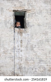 FEZ, MOROCCO - ENERO 14, 2015: Portrait of unidentified boy with a toy gun in a window. Morocco is a Muslim country where the extremist of Islam is still not widespread