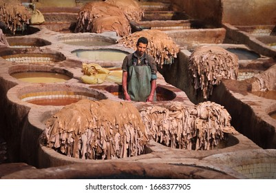 FEZ, MOROCCO – FEB 08: Unidentified man works at the famous Chouara Tannery on February 08, 2020 in historical center, ancient Medina of Fes, Morocco, North West Africa.