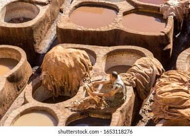 Fez, Morocco  - February 23. 2019: Traditional leather tannery in Fez with a worker working in old leather making methods.
