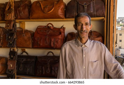 FEZ, MOROCCO - MAY 14, 2017: a leather seller in front of his hand made leather products.  Fez has several traditional leather tanneries, many of which are cooperatives.