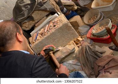 Fez, Morocco - November 19, 2011: Craftsman freehand chiseling glazed terra cotta pieces for Zellige tilework Fes Morocco