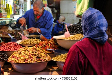 Fez, Morocco - November 8, 2017: Muslim lady buying olives at the Fez Medina market. The Medina of Fez is the biggest urban zone in the world that is restricted to traffic. Credit: Dino Geromella