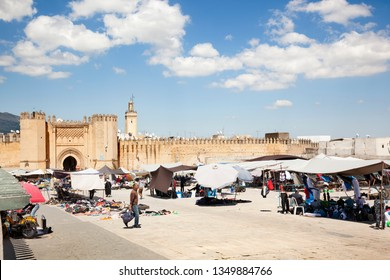 FEZ, MOROCCO-APRIL 23, 2014: Moroccans selling clothes on local market, many people watching and buying; Fes-Boulemane región, North Africa on April 23, 2014