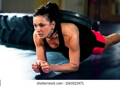 Ffitness girl doing hard crossfit exercises in dark gym