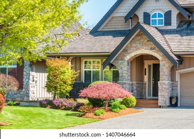 Fgrament of beautiful exterior of newly built luxury home. Yard with green grass and landscape.