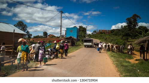 FIANARANTSOA / MADAGASCAR - 23 DECEMBER 2013: Rural African road with villagers walk on the sidewalk, car and cows