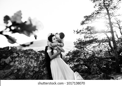 fiance from behind hugs a bride, a walk in the mountains in the spring, black and white photo