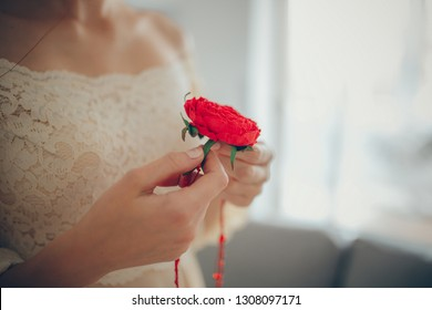 Fiancee holding buttonhole bouquet in hands.
