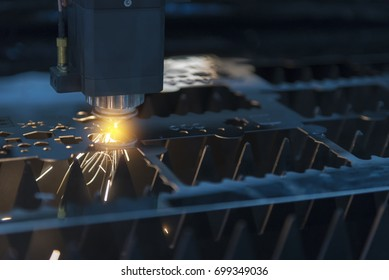 The fiber  laser cutting machine  cutting the sheet metal plate with the sparking light.Hi-technology manufacturing concept.