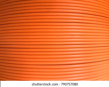 Fiber optic cables are arranged in rolls, Orange background with Fiber optic cables