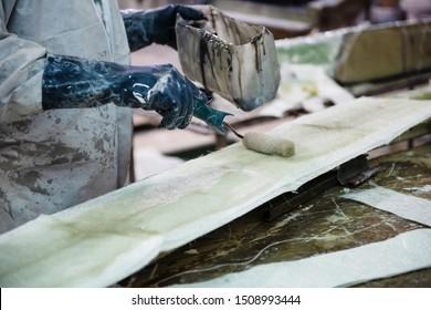 Fiberglass factory worker in gloves rolls solution through fiberglass sheets
