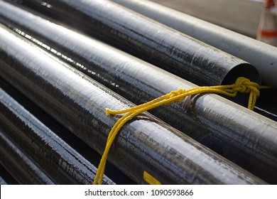 Fiberglass pipes bound with yellow rope at construction site. Also known as fiberglass conduit for electrical, industrial, and mechanical use.