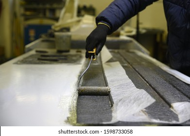 Fiberglass processing: worker manually realizes a component in glass fiber. White glass fiber composite raw material background. Working with the brush and with the resin.