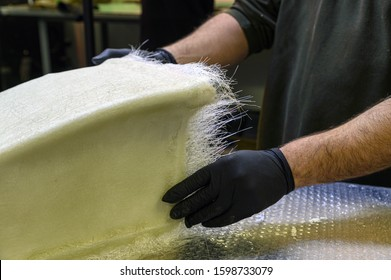 Fiberglass processing: worker manually realizes a component in glass fiber. Emplyee working with fiber glass for cut material. White glass fiber composite raw material background.