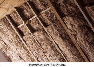 Fiberglass is used as warming mineral material on a ceiling in a private house. Glass wool in a wooden frame on a wall.