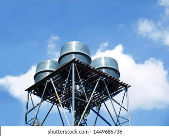 Fiberglass water tank on the tower Outdoor water storage tanks for storing water and use in villages or communities On a blue sky background and white clouds with a copy area. selective focus
