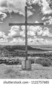FICKSBURG, SOUTH AFRICA - MARCH 12, 2018:  A wooden cross with the Ten Commandments engraved on a granite scroll with the central business district of Ficksburg in the back. Monochrome