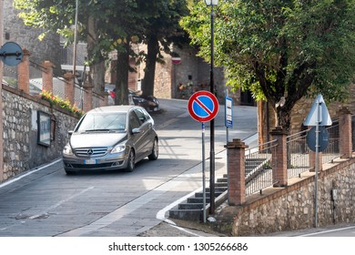 Ficulle, Italy - September 3, 2018: Street in Umbria historic small town village with car on road in traffic and no entrance sign