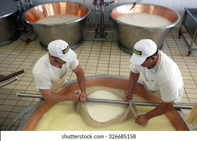 FIDENZA, ITALY - 11 SEPTEMBER 2014: Workers move curd into a gauze ahead of lifting from a copper vat during the Parmigiano-Reggiano cheese manufacturing process at a cheese factory.