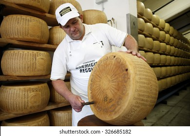 FIDENZA, ITALY - 11 SEPTEMBER 2014: Parmigiano-Reggiano cheeses sit on storage racks during the aging process at a cheese factory.