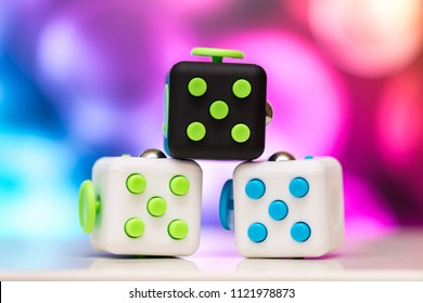 Fidget cube antis stress toy. Detail of finger play toy used for relax. Gadget placed on colorful bokeh background.