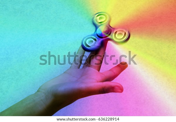 Fidget spinner or hand spinner, fidgeting hand toy rotating on child's hand